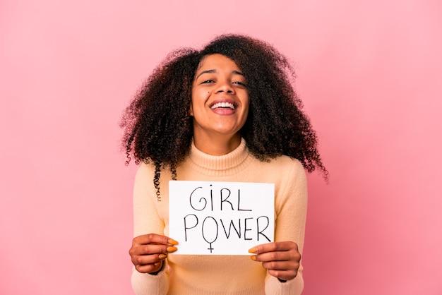 笑って楽しんでいるプラカードに女の子のパワーメッセージを保持している若いアフリカ系アメリカ人の巻き毛の女性。