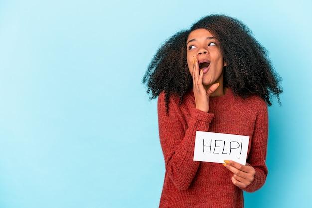도움말 현수막을 들고 젊은 아프리카 계 미국인 곱슬 여자는 비밀 뜨거운 제동 뉴스를 말하고 옆으로보고있다