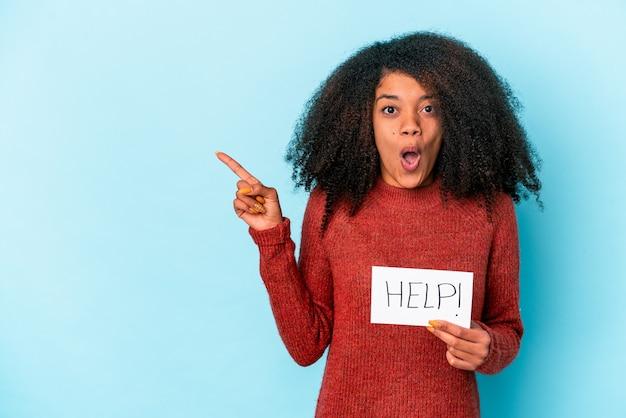 측면을 가리키는 도움말 현수막을 들고 젊은 아프리카 계 미국인 곱슬 여자