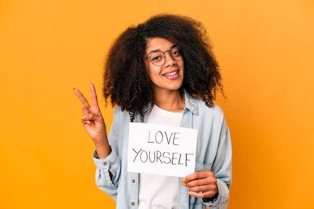 指で2番目を示す自分自身の愛のプラカードを保持している若いアフリカ系アメリカ人の巻き毛の女性。