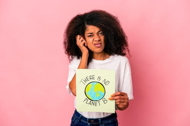 手で耳を覆うプラカードに惑星のメッセージを保持している若いアフリカ系アメリカ人の巻き毛の女性。