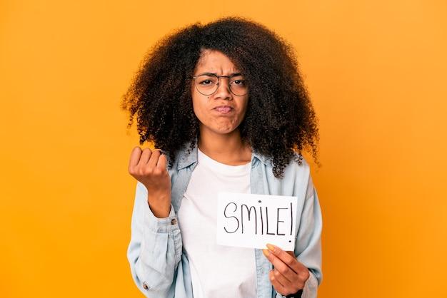 주먹, 공격적인 표정을 보여주는 미소 메시지 현수막을 들고 젊은 아프리카 계 미국인 곱슬 여자.