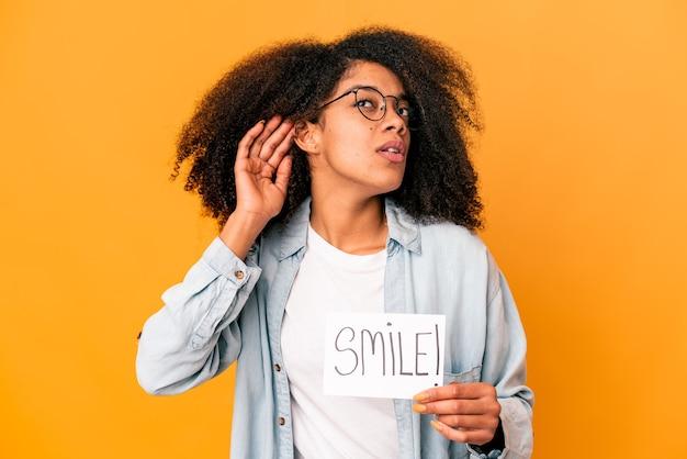 Молодая афро-американская кудрявая женщина, держащая плакат с улыбкой, пытается слушать сплетни.