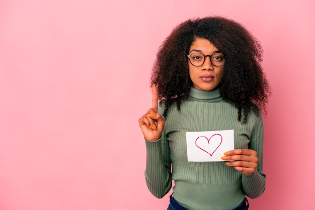 Young african american curly woman holding a heart symbol on placard showing number one with finger.