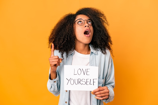 Young african american curly woman holding a love yourself placard pointing upside with opened mouth.