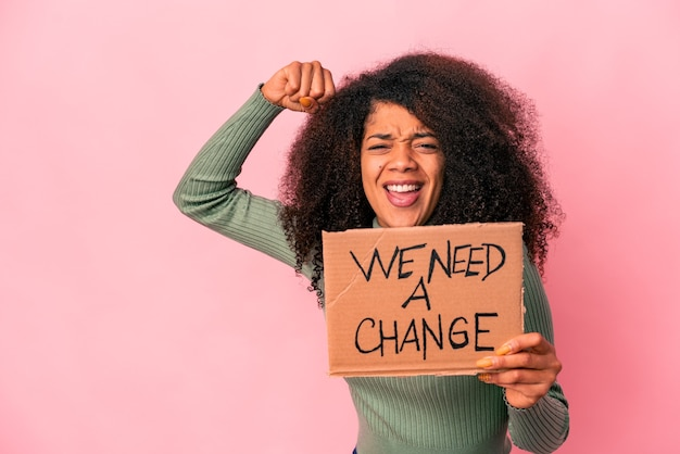 Young african american curly woman holding a we need a change cardboard raising fist after a victory, winner concept.