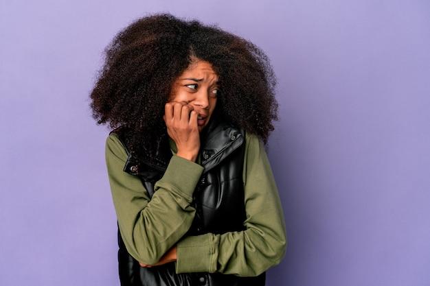 若いアフリカ系アメリカ人の巻き毛の女性は、紫色の背景に爪を噛んで孤立し、神経質で非常に心配しています。