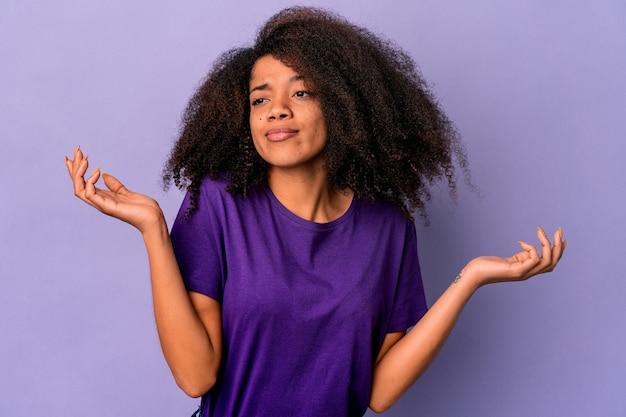 Молодая афро-американская кудрявая женщина, изолированная на фиолетовом фоне, смущает и сомнительно пожимает плечами, чтобы провести копию пространства.