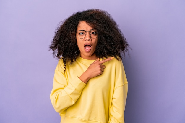 Молодая афро-американская фигурная женщина изолирована на фиолетовом фоне, указывая в сторону