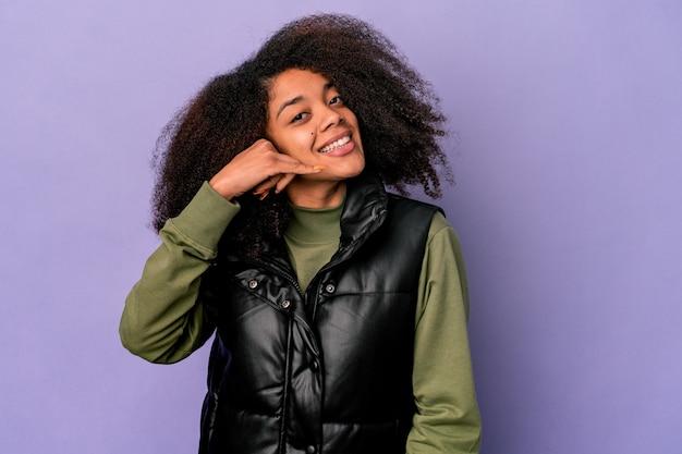 指で携帯電話の呼び出しジェスチャーを示す紫色の背景に分離された若いアフリカ系アメリカ人の巻き毛の女性。