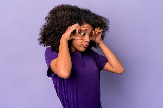 Молодая афро-американская кудрявая женщина изолирована на фиолетовом, держа глаза открытыми, чтобы найти возможность успеха.