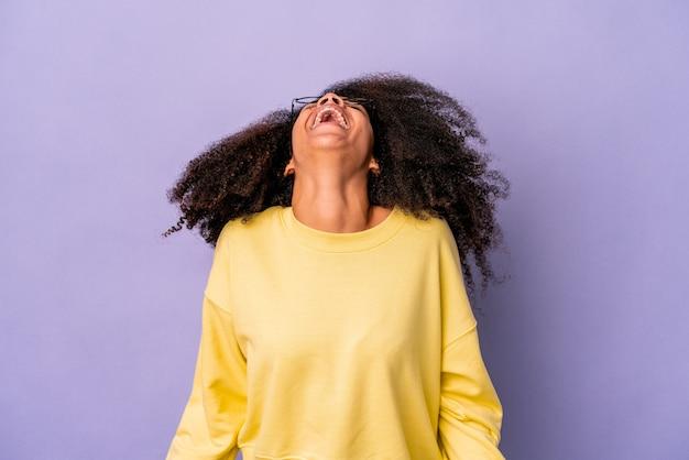 紫色のリラックスした幸せな笑いで孤立した若いアフリカ系アメリカ人の巻き毛の女性、首を伸ばして歯を見せています。