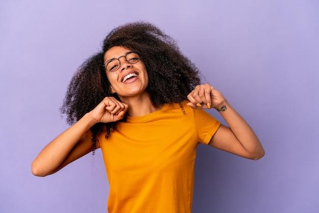 Молодая афро-американская фигурная женщина, изолированная на фиолетовой стене, танцует и веселится.