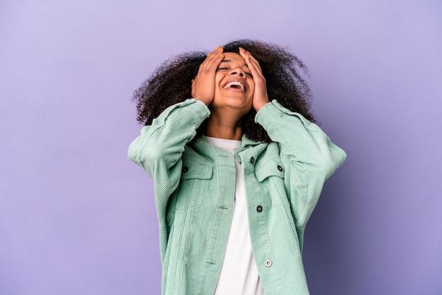 紫色の壁に隔離された若いアフリカ系アメリカ人の巻き毛の女性は、頭に手を置いて喜んで笑います。幸福の概念。