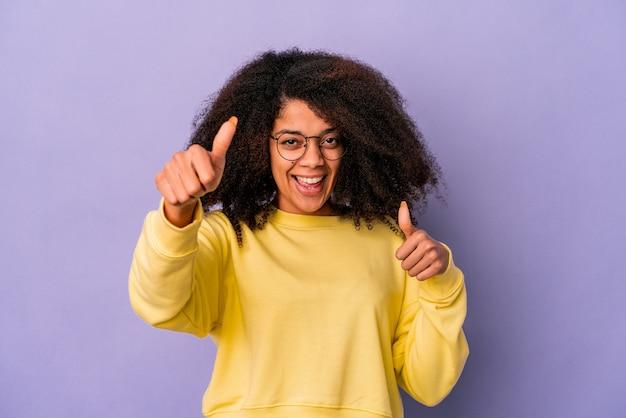 紫色の壁に孤立した若いアフリカ系アメリカ人の巻き毛の女性は、両方の親指を上げて、笑顔で自信を持っています。 Premium写真
