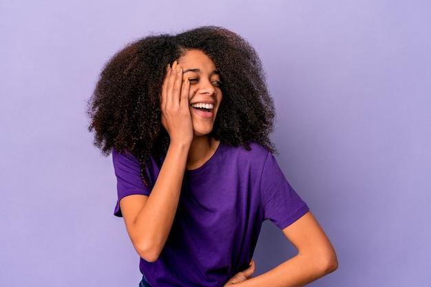 Молодая афро-американская фигурная женщина, изолированная на фиолетовой стене крича, возбужденной вперед.