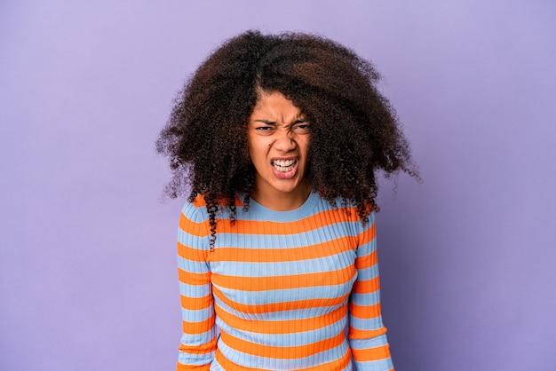 Молодая афро-американская кудрявая женщина, изолированная на фиолетовой стене, кричала очень сердито, концепция ярости, разочарована.
