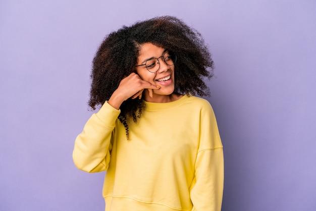 紫色の壁に隔離された若いアフリカ系アメリカ人の巻き毛の女性、指で携帯電話の呼び出しジェスチャーを示しています。
