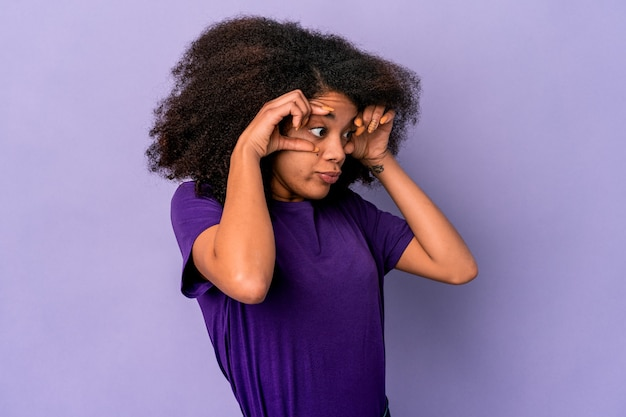 Young african american curly woman isolated on purple keeping eyes opened to find a success opportunity.