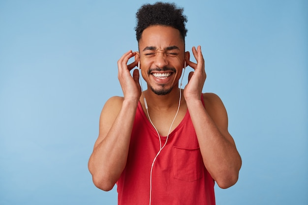 Young african american dark skinned man feels great and very happy, close eyes, listens to your favorite song and sings along, smiles, stands.