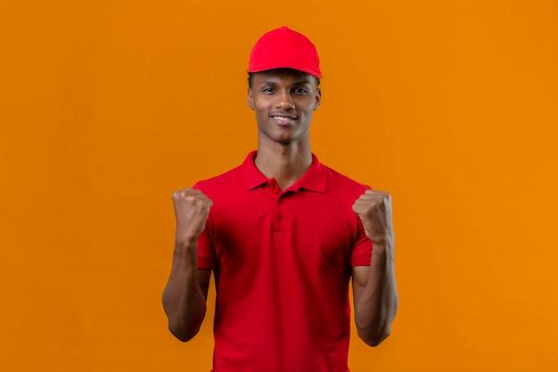 Молодой афро-американский работник доставляющий покупки на дом нося красную рубашку поло и крышку уверенно смотря стоящ с концепцией победителя поднимать кулаков над изолированным апельсином