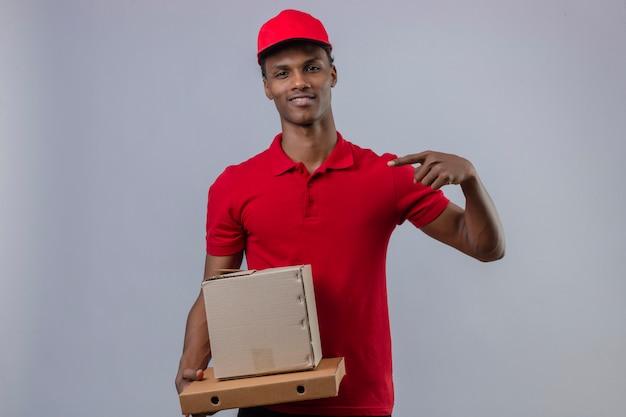 Молодой афроамериканец доставляющий носить красную рубашку поло и шапку, держа коробки, глядя уверенно указывая пальцем на себя над изолированной белой