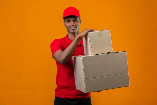 Молодой афроамериканец доставляющий носить красную рубашку поло и кепку, держа коробки с большой улыбкой над изолированным апельсином
