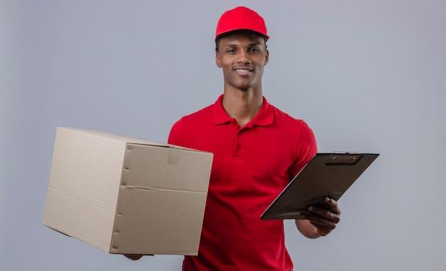 Молодой афроамериканец доставки человек, одетый в красную рубашку поло и шапку, держа картонную коробку и буфер обмена с улыбкой на лице, стоя над изолированных белый