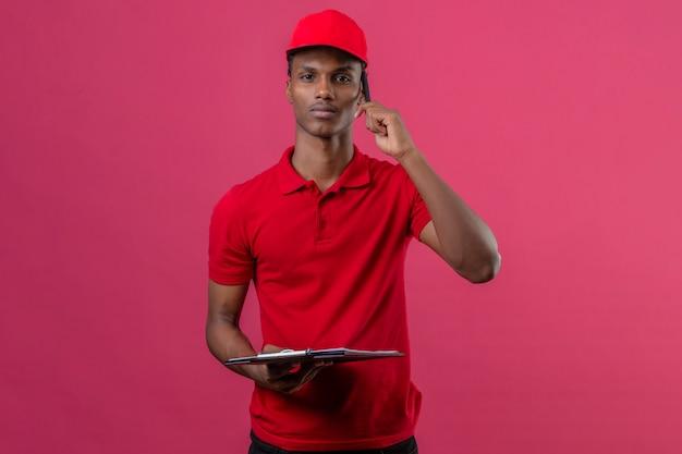Молодой афроамериканец доставки человек, одетый в красную рубашку поло и шапку, держа буфера обмена и пятнышек на смартфон с серьезным лицом на изолированных розовый