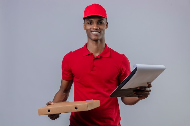 Молодой афроамериканец доставляющий носить красную рубашку поло и кепку, держа коробку для пиццы и буфера обмена с улыбкой на лице на белом фоне
