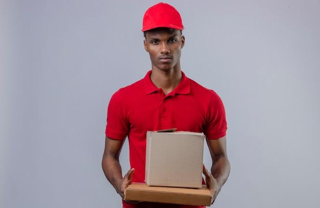 Молодой афроамериканец доставляющий носить красную рубашку поло и шапку, держа стопку картонных коробок, глядя на камеру с серьезным лицом над изолированной белой
