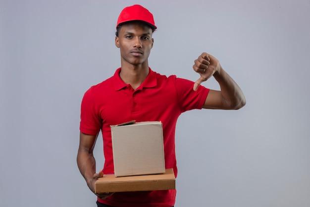 Молодой афроамериканец доставляющий носить красную рубашку поло и шапку, держа стопку картонных коробок, показывая большой палец вниз с серьезным лицом на белом фоне