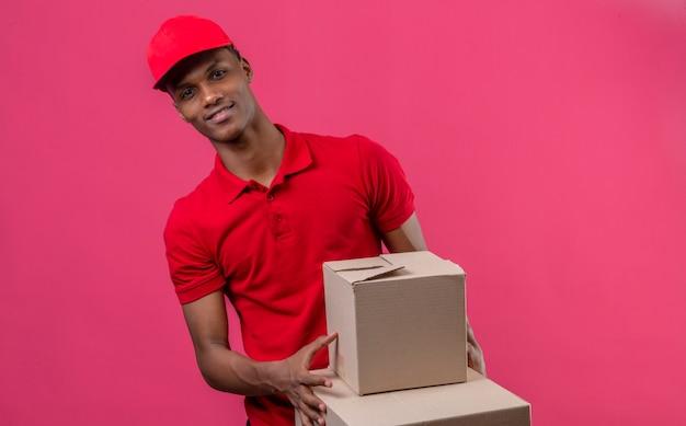Молодой афроамериканец доставки человек, одетый в красную рубашку поло и шапку, держа стопку картонных коробок, улыбаясь, глядя на камеру над изолированных розовый