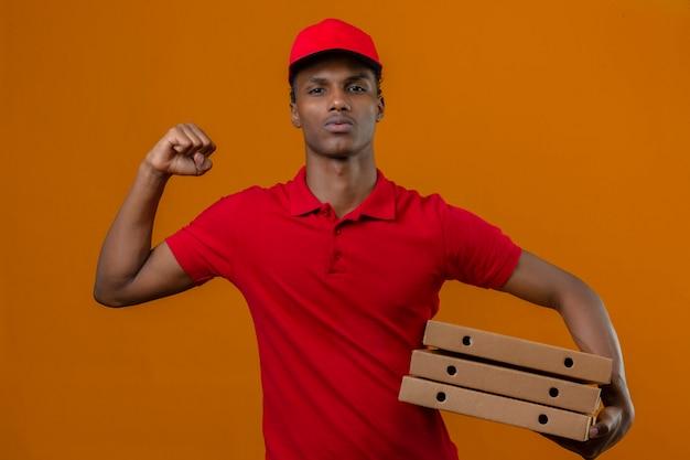 Молодой афро-американский работник доставляющий покупки на дом нося красную рубашку поло и крышку удерживания стог коробок для пиццы с поднятой концепцией победы кулака над изолированным апельсином
