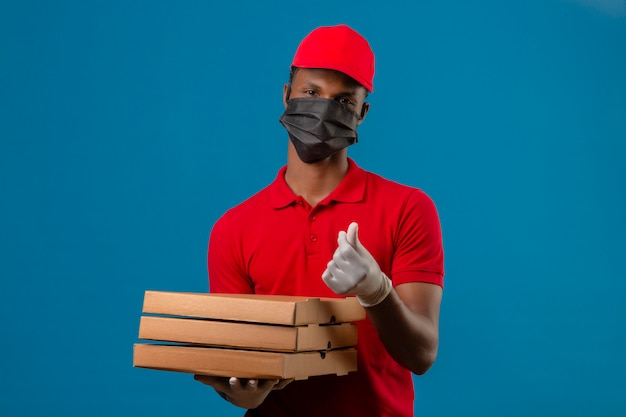 Молодой афроамериканец доставляющий носить красную рубашку поло и шапку в защитной маске и перчатки, стоя с стопку коробок для пиццы, делая деньги жест над изолированной синей