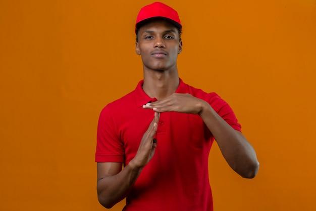 Молодой афро-американский работник доставляющий покупки на дом нося красную рубашку поло и крышку смотря перегружанный показывающ жест перерыва над изолированным апельсином