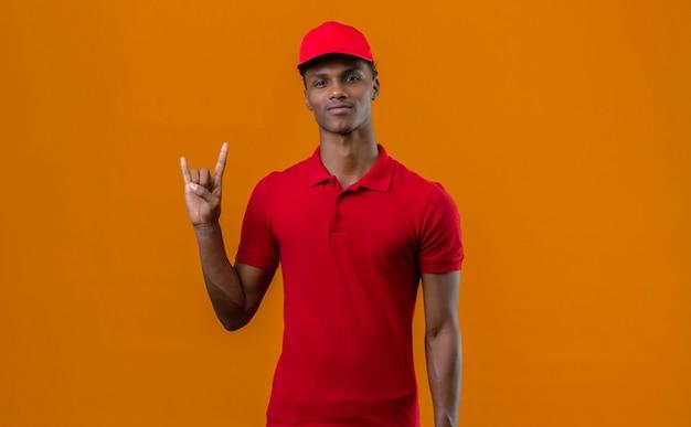 Молодой афро-американский работник доставляющий покупки на дом нося красную рубашку поло и крышку делая жест утеса стоя над изолированным апельсином