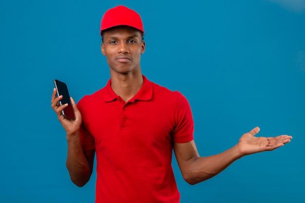 赤のポロシャツとスマートフォンで立っているキャップを身に着けている若いアフリカ系アメリカ人の配達人の手で混乱していると分離された青に疑問を持っている