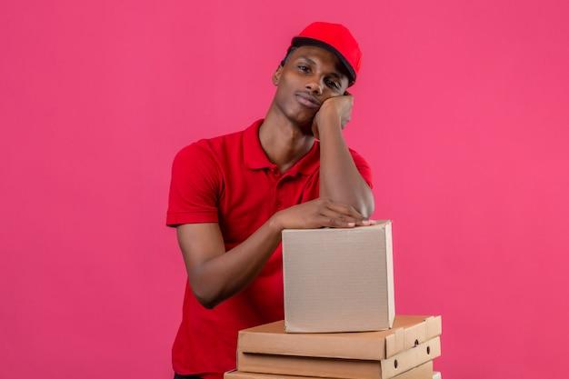 赤いポロシャツと待っているキャップを着ている若いアフリカ系アメリカ人の配達人は分離されたピンクの上に段ボール箱に彼の肘を突いた