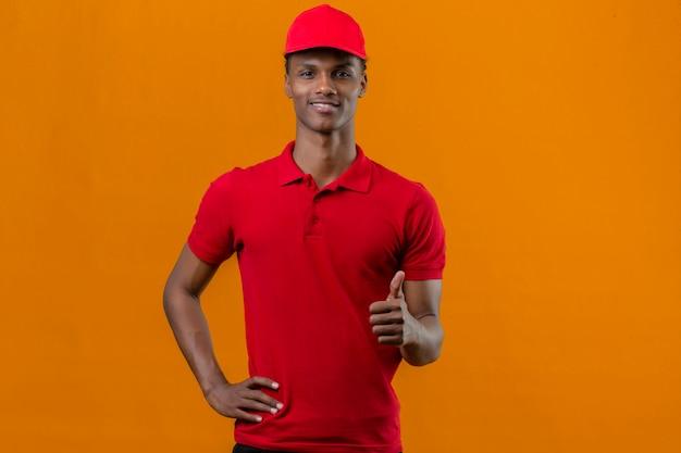 孤立したオレンジの上のカメラまで親指を示す顔に赤いポロシャツと笑顔でキャップを着ている若いアフリカ系アメリカ人の配達人