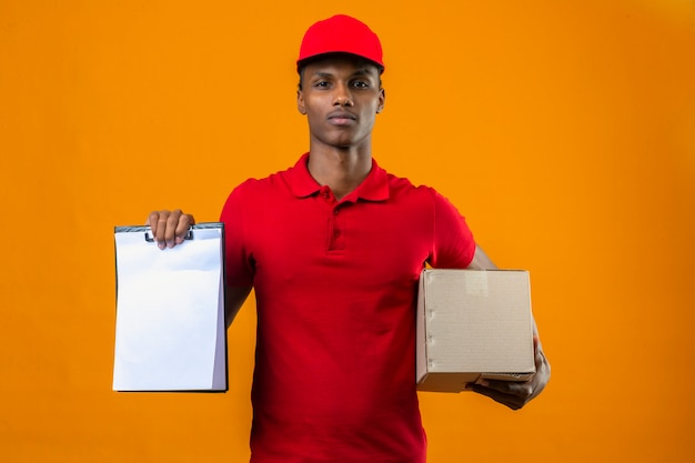 Young african american delivery man wearing red polo shirt and cap holding box package and clipboard with empty blanks looking confident over isolated orange