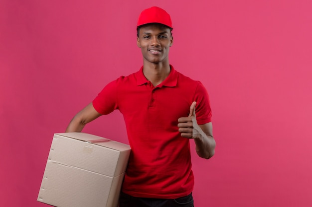 Young african american delivery man wearing red polo shirt and cap holding cardboard box and showing thumb up over isolated pink
