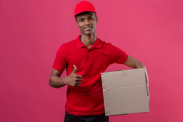 Young african american delivery man wearing red polo shirt and cap holding cardboard box showing thumb up with smile on face over isolated pink