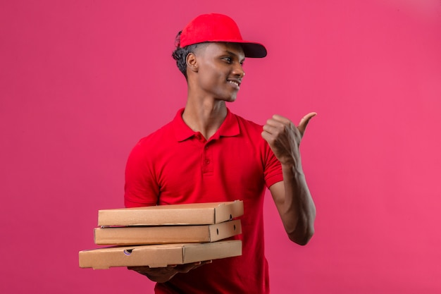 Young african american delivery man wearing red polo shirt and cap holding stack of pizza boxes looking away pointing with finger to side with smile on face over isolated pink