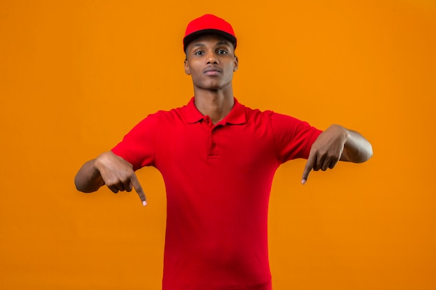 Young african american delivery man wearing red polo shirt and cap and pointing fingers down over isolated orange