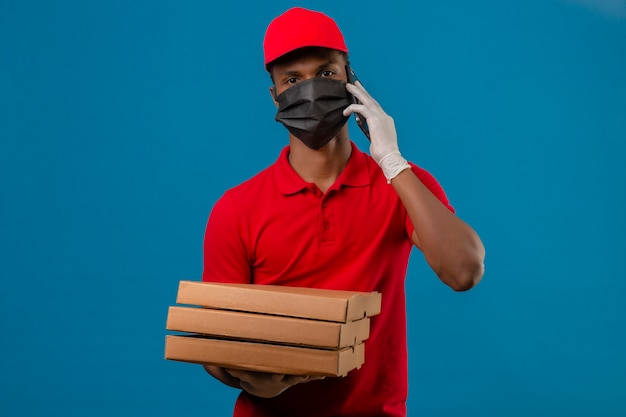 Young african american delivery man wearing red polo shirt and cap in protective mask and gloves carrying stack of pizza boxes while speaking by smartphone over isolated blue