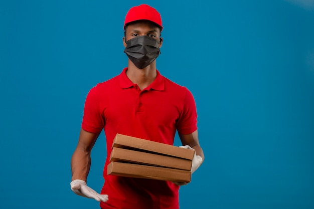 Young african american delivery man wearing red polo shirt and cap in protective mask and gloves standing with stack of pizza boxes over isolated blue