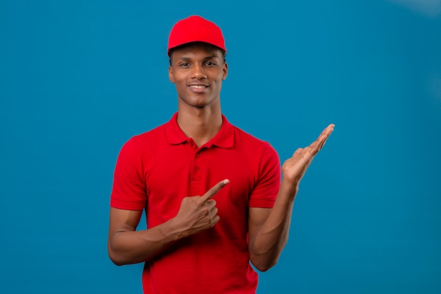 Young african american delivery man wearing red polo shirt and cap showing and pointing to side watching at camera with smile on face over isolated blue