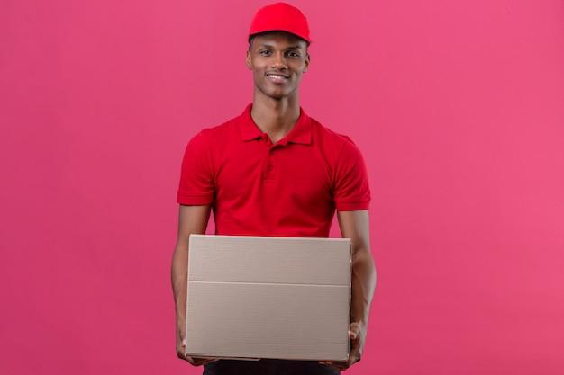 Giovane fattorino afroamericano che indossa la camicia e il cappuccio di polo rossi che stanno con la scatola di cartone che sorride sopra il rosa isolato