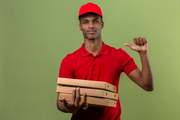 Young african american delivery man wearing red polo shirt and cap standing with stack of pizza boxes pointing finger to himself confident looking over isolated green
